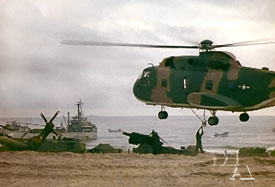 Vietnam photo of a USAF CH-3 Jolly Green Giant lifting a Marine artillery piece off the beach